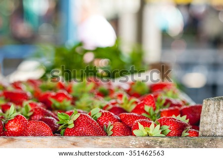 Red ripe juicy strawberries in wooden baskets on the marketplace with blurred background - stock photo