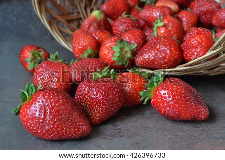 Red ripe strawberries are on the wicker basket.  The most popular berry fruits in the world.  An excellent source of vitamins C and K. - stock photo