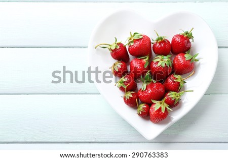 Red ripe strawberries on heart shaped plate, on color wooden background - stock photo