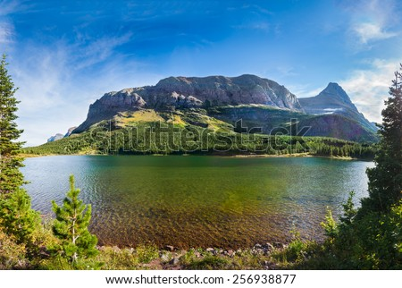 Red rocks, pine trees, and clear green water at Red Rock Lake in Glacier National Park, Montana - stock photo