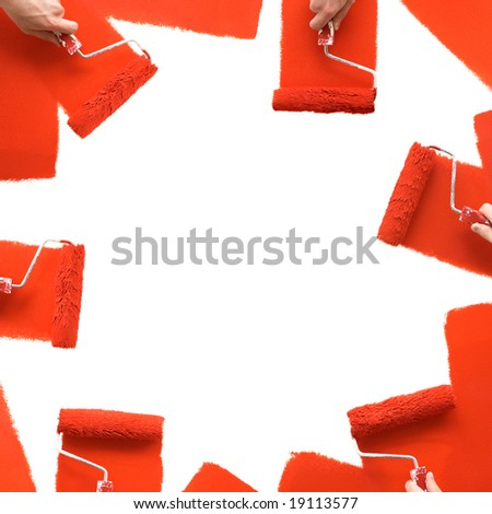 Red rollers paint the wall - stock photo