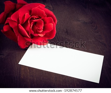 red rose and blank gift card for text on old wood background, valentine day and love concept - stock photo