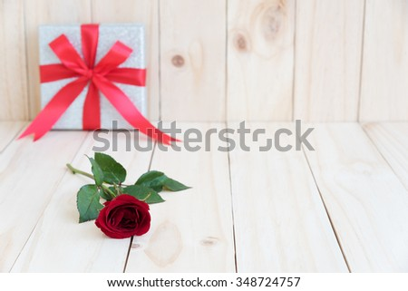 red rose and present on wooden background with space, love concept for valentines day, wedding and anniversary - stock photo