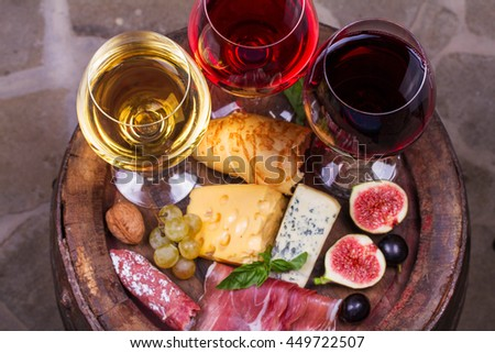 Red, rose and white glasses and bottles of wine. Cheese, fig, grape, prosciutto and bread on old wooden barrel. View from above, top studio shot of vegetables and fruits  - stock photo