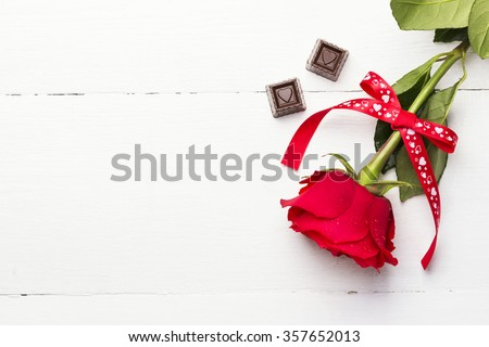 Red rose, chocolates on a white wooden background - stock photo