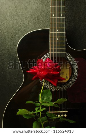 Red rose on a black acoustic guitar - stock photo