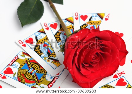 Red rose over playing card of heart - stock photo