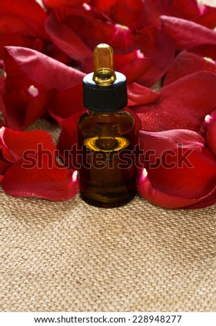 Red rose petals and massage oil on sackcloth - stock photo