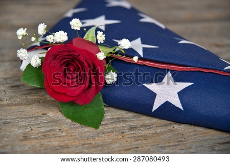 red rose tucked inside a folded American flag - stock photo