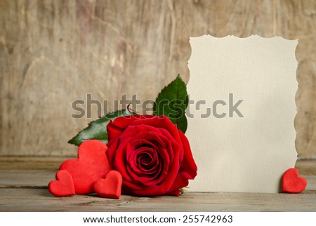 Red rose with paper for text and handemade valentines around on wooden background - stock photo