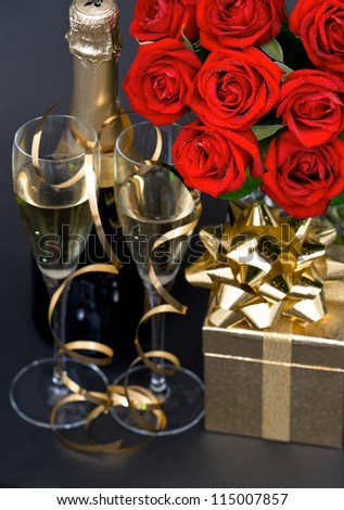 red roses and champagne on black background. festive decoration. romantic arrangement. selective focus - stock photo