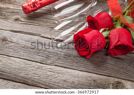 Red roses and champagne over wooden background. View with copy space - stock photo