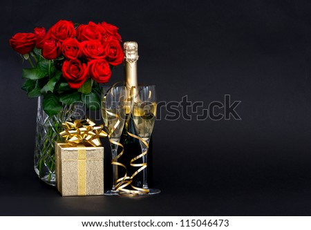 red roses and champagne with golden decoration on black background. romantic arrangement. space for your text. selective focus - stock photo