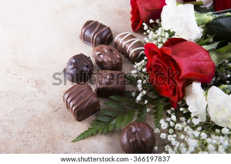 Red roses and chocolate candy for your sweetheart. - stock photo