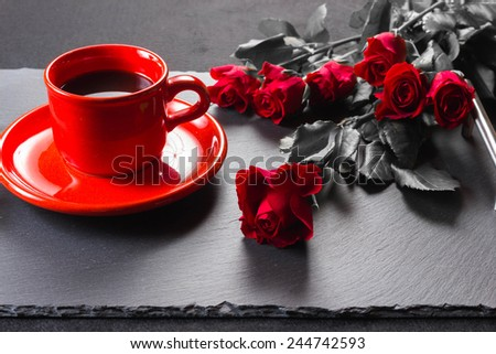 Red roses and coffee on slate tray, red,black and white - stock photo
