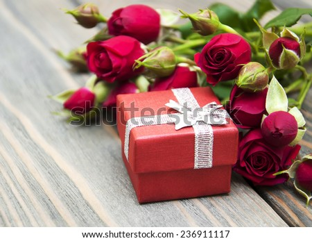 Red roses  and gift box on a wooden background - stock photo