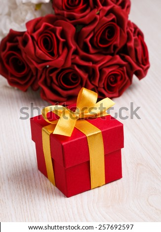 red roses and red gift box with yellow ribbon on wooden surface - stock photo