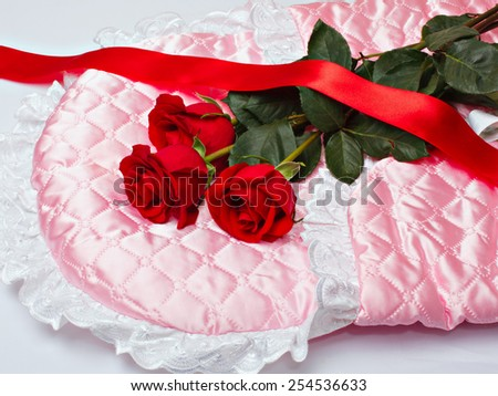 Red roses and scarlet ribbon on pink satin. New born concept.