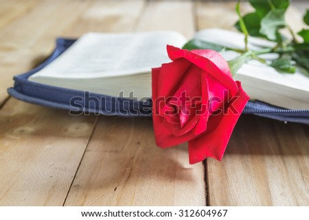 Red roses close up with book on wooden background. - stock photo