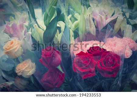 red roses flowers bouquet in plastic wrap by pastel vintage color process - stock photo