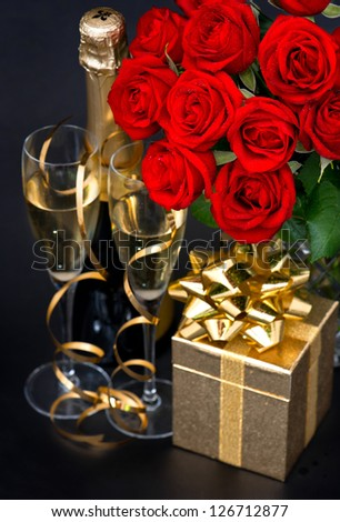 red roses, golden gift and and champagne on black background. St. Valentine's Day card concept - stock photo