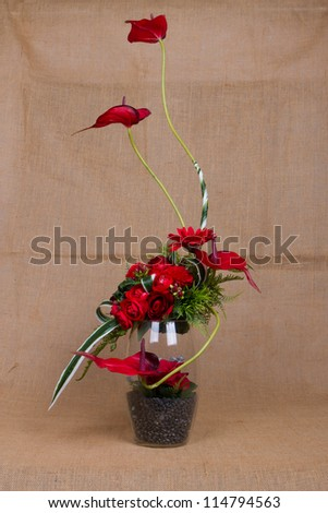 Red roses in glass jars on sackcloth - stock photo