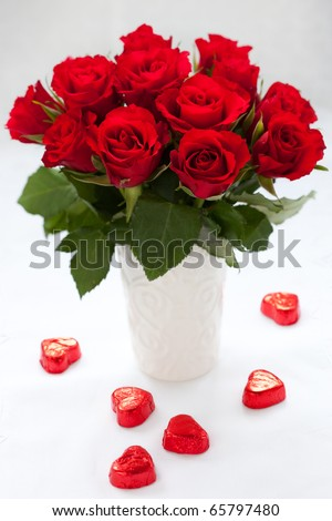 red roses in vase and chocolate candies for Valentine's Day - stock photo
