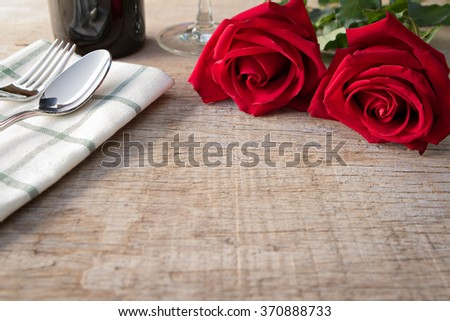 Red roses on dining table.  Valentine's Day, anniversary etc. - stock photo