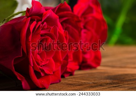Red roses on wooden table with narrow focus - stock photo