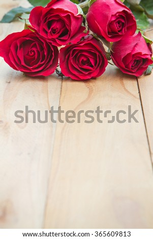 Red roses on woonden background. Valentine's day background. - stock photo