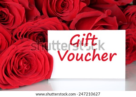 Red roses with gift voucher certificate for birthday, Valentine's or mothers day - stock photo