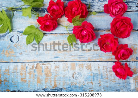 Red roses with green leaves on wooden background - stock photo