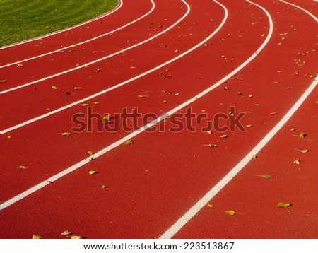 Red Running Track with white lines  at stadium - stock photo