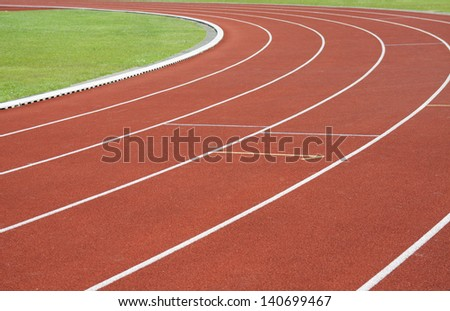 Red running tracks with green grass  and white lines - stock photo