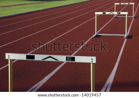 red running tracks with three hurdles set up for training - stock photo
