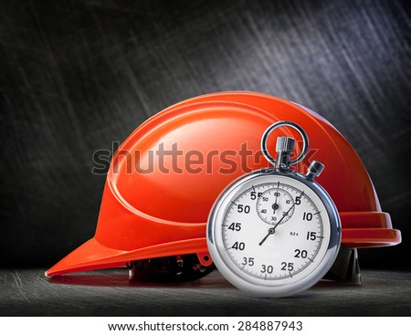Red safety helmet and stopwatch on steel background - stock photo