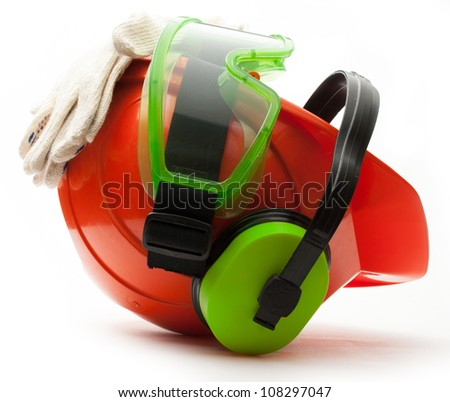 Red safety helmet with earphones, goggles and gloves - stock photo