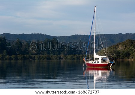 Red sail yacht mooring in the bay of Islands New Zealand. horizontal - stock photo