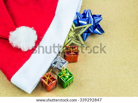 Red Santa Claus hat and gift box on wooden table background - stock photo