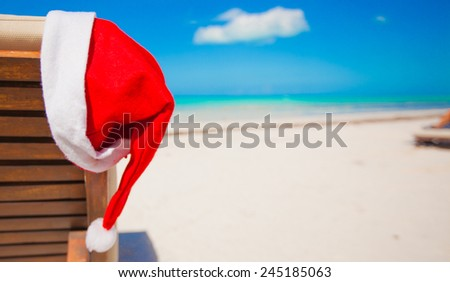 Red santa hat on chair longue at tropical caribbean beach - stock photo