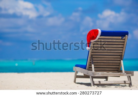 Red santa hat on chair longue at tropical white beach - stock photo