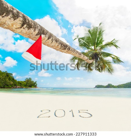 Red Santa hat on palm tree at exotic tropical beach and 2015 year sand caption. Holiday concept for New Years Cards. Seychelles, Mahe. - stock photo