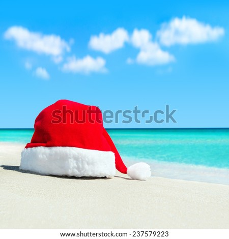Red santa hat on white tropical beach sand - Christmas or New Year's vacation in hot countries concept - stock photo