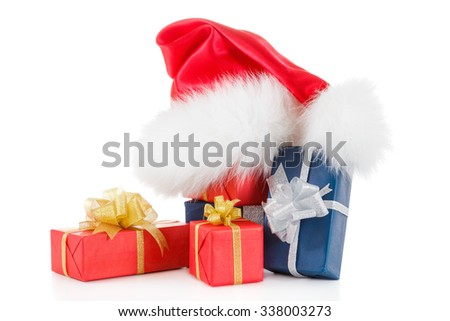 Red santa hat with gift boxes. Silver and gold ribbons. Isolated on white background closeup - stock photo