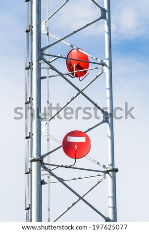 Red satellite dishes on mobile phone tower  - stock photo