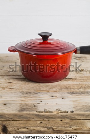 Red saucepan and its lid - stock photo