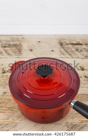 Red saucepan on table - stock photo