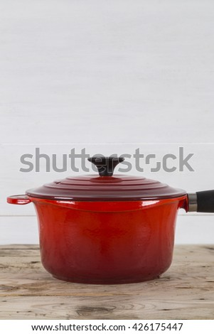 Red saucepan with lid on table - stock photo