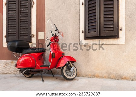 Red scooter parked by the wall in the empty street. - stock photo
