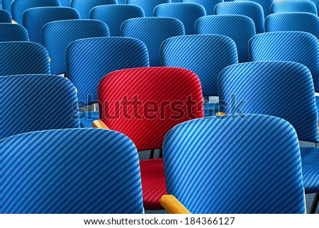 Red seat as an eyecatcher in the middle of rows of empty blue seats, conceptual image - stock photo
